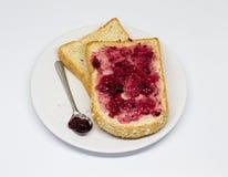 Brot mit Verbreitungsstau auf dem Teller auf weißem Isolathintergrund Lizenzfreie Stockfotos