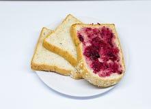 Brot mit Verbreitungsstau auf dem Teller auf weißem Isolathintergrund Stockfotos