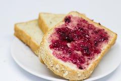 Brot mit Verbreitungsstau auf dem Teller auf weißem Isolathintergrund Stockfoto