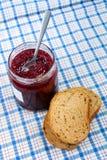 Brot und Glas mit Himbeermarmelade auf blauer Tischdecke Lizenzfreie Stockfotografie