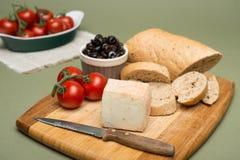 Brot und Käse/köstlicher organischer Sahnemilchkäse, Oliven und selbst gemachte Brot- und reifetomaten auf hölzernem Brett stockbild