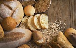 Brot und Körner zerstreut auf den Holztisch Lizenzfreie Stockfotografie