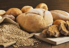 Brot und Körner zerstreut auf den Holztisch Lizenzfreies Stockbild