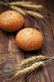 Brot und Weizenähren auf einem Holztisch Stockfoto