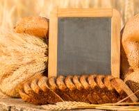 Brot und Weizen auf dem Holztisch Stockbilder
