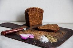 Brot und Zwiebeln auf einem Schneidebrettsalz Lizenzfreies Stockbild