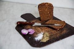 Brot und Zwiebeln auf einem Schneidebrettsalz Stockfotos