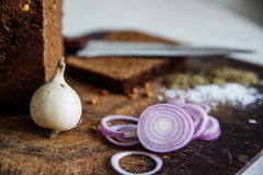 Brot und Zwiebeln auf einem Schneidebrettsalz Stockfoto