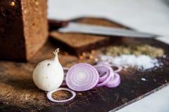 Brot und Zwiebeln auf einem Schneidebrettsalz Stockbilder