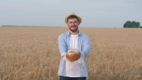 Brotbackautomatporträt, junger Kerl im Strohhut gibt Ihnen frisch gebackenes Brot und Lächeln an der Kamera auf dem Weizenerntege stock footage