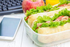 Brotdose mit ciabatta Brotsandwichen, Apfel und Orangensaft Lizenzfreies Stockbild