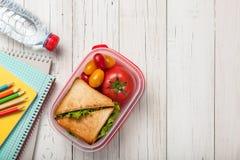 Brotdose mit Sandwich und Tomaten, Schulbedarf und Wasser Lizenzfreies Stockbild