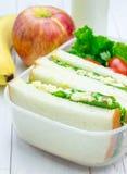 Brotdose mit Sandwichen, Apfel, Banane und Milch Lizenzfreie Stockfotografie