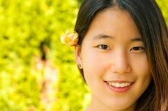 Brote asiático joven de Rose de la mujer en pelo Fotografía de archivo
