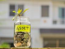 Brote el crecimiento de monedas en el tarro de cristal contra backge de la casa de la falta de definición Foto de archivo libre de regalías