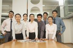 Büroteam, das nahe dem Schreibtisch, Porträt steht Stockfotos