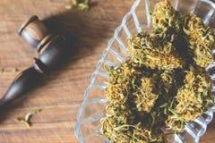 Brotes de la marijuana en la placa de cristal Foto de archivo libre de regalías