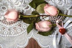Brotes de rosas rosadas y corazón rojo con las cintas Imágenes de archivo libres de regalías