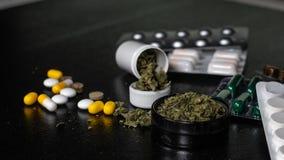 Brotes médicos de la marijuana en cada equipo de primeros auxilios las píldoras y los cáñamos mienten en un fondo negro La atenci imágenes de archivo libres de regalías