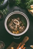 Broth of beef meat shin with bone in cooking pot on dark kitchen table background with ingredients for soup, top view. Meat broth. Or stock. Clean low-calorie stock photos