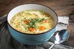 Broth - chicken soup in a blue bowl. Broth - chicken soup with noodles in a blue bowl Stock Photo