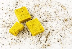 Broth cubes. Three cubes of broth on the background of scattered hammer pepper Royalty Free Stock Photography