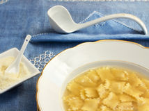 Broth with ravioli over blue linen tablecloth Royalty Free Stock Photos
