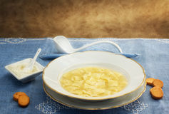 Broth with ravioli over blue linen tablecloth Royalty Free Stock Photography