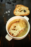 Broth with toasts of bread and black olives royalty free stock photos