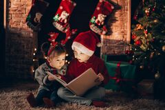 Free Brother And Sister Are Sitting And Reading A Book. Christmas Mood. Children In New Year`s Costumes Against The Background Of A Stock Photo - 201520630