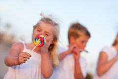 Brother And Sisters Enjoying Their Lollipops Outsi