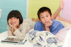 Brother ans sister siblings together on bed Royalty Free Stock Image
