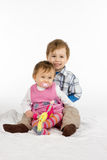 Brother and baby sister. Big brother holding his baby sister on his lap Royalty Free Stock Images