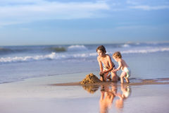 Brother and baby sister building a sand castle Stock Photography