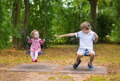 Brother and baby sister on swing on playground Stock Photography