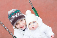 Brother and baby sister swinging in a park Stock Photo