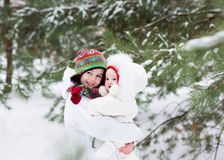 Brother and baby sister walking in forest on snowy winter day Stock Image