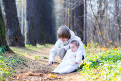Brother and baby sister in white jackets playing in a park Stock Photos