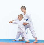 Brother with a blue belt teaches the brother with a white belt to beat the punch arm Royalty Free Stock Image
