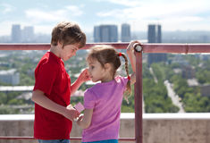 Brother with camera touch sister on roof Royalty Free Stock Photo