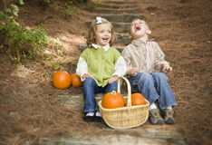Brother de risa y hermana Children Sitting en los pasos de madera con las calabazas Foto de archivo libre de regalías