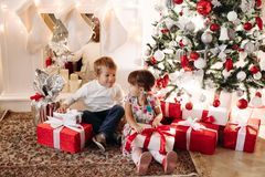 Brother in deer Christmas hat kissing his younger sister in head royalty free stock images
