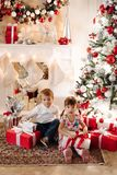 Brother in deer Christmas hat kissing his younger sister in head stock images