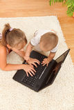 Brother disturbing his sister. Top view of a girl typing on laptop while her brother is disturbing herself by touching the keys Royalty Free Stock Photos