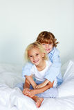 Brother embracing her sister in bed. Little brother embracing her little sister in bed Royalty Free Stock Photography