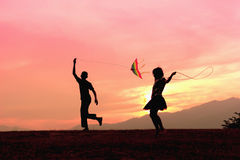 A brother getting a kite to fly and sister rope jumping during. Sunset stock image