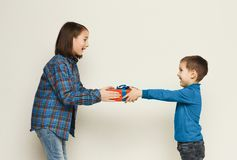Brother giving his sister gift, white studio. Cute little boy giving his sister gift, white studio background. Birthday celebration, brother congratulating his stock images