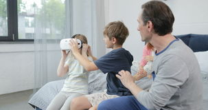 Brother Giving Sister Virtual Reality Glasses While Spending Morning With Parents In Bedroom Family Entertainment stock video
