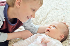 Brother glad to see baby sister Stock Image