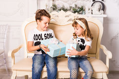 Brother is going to give his sister a gift for Christmas or New Year. Royalty Free Stock Images